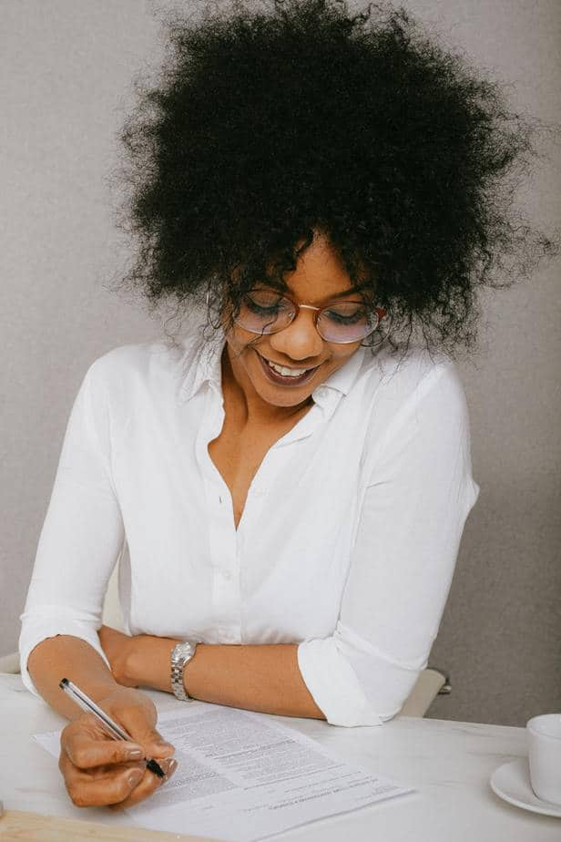 Black woman in white blouse signing contract