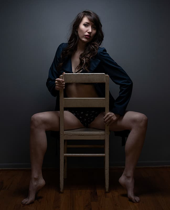 Boudoir chair pose with woman straddling chair