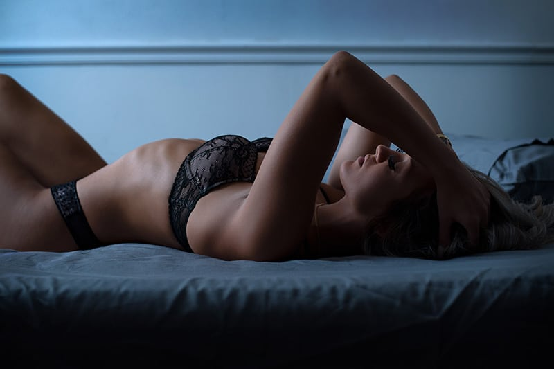 Dark and moody boudoir with dark sheets and lingerie
