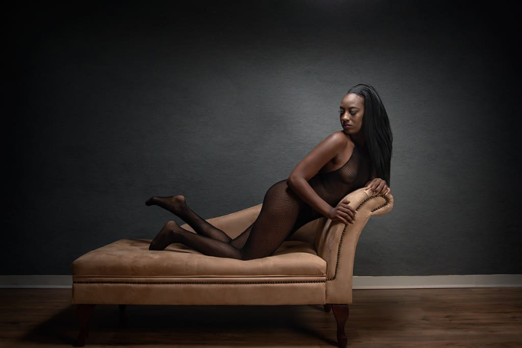 Kneeling boudoir pose on chaise lounge