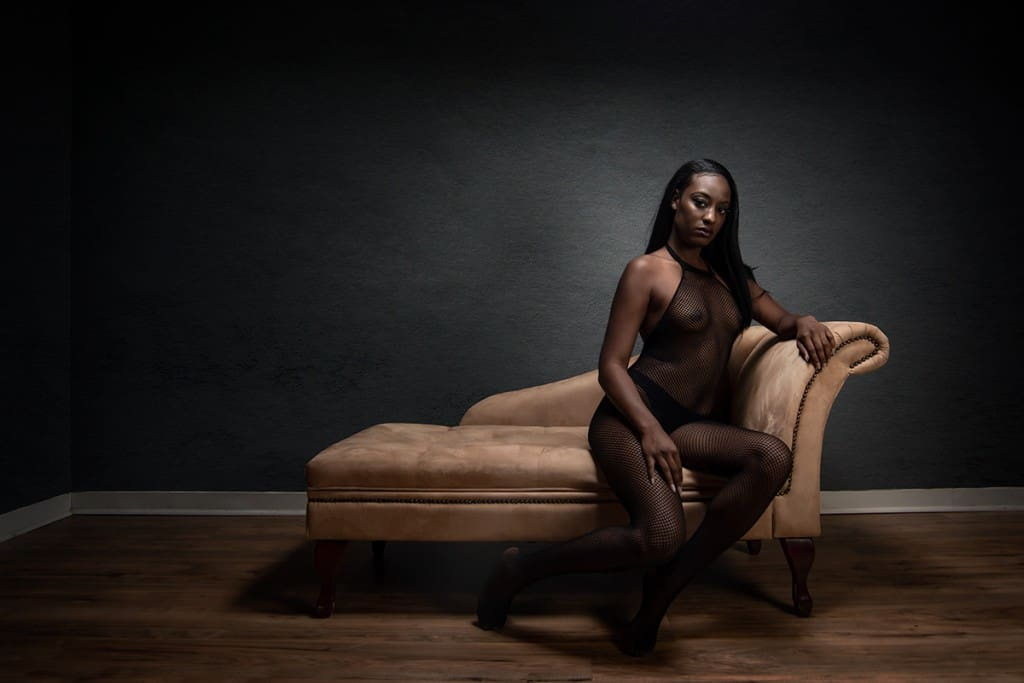 Seated boudoir pose on chaise lounge.